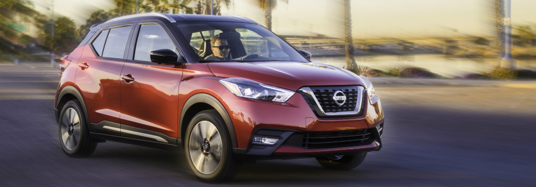 orange 2018 nissan kicks driving on road with palm trees in background