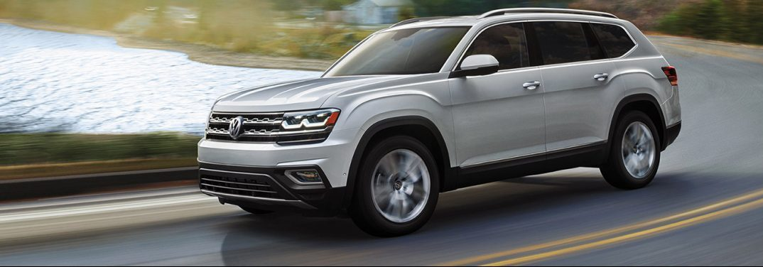 Silver 2019 Volkswagen Atlas smoothly taking a highway curve with a lake in the background.