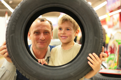 A man and a child hold a tire together and stare through the center of it.
