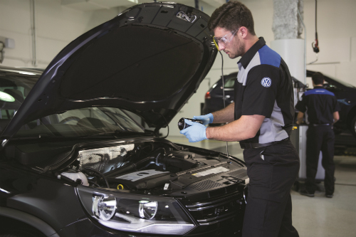 A mechanic examines the engine and under-hood area of a vehice.