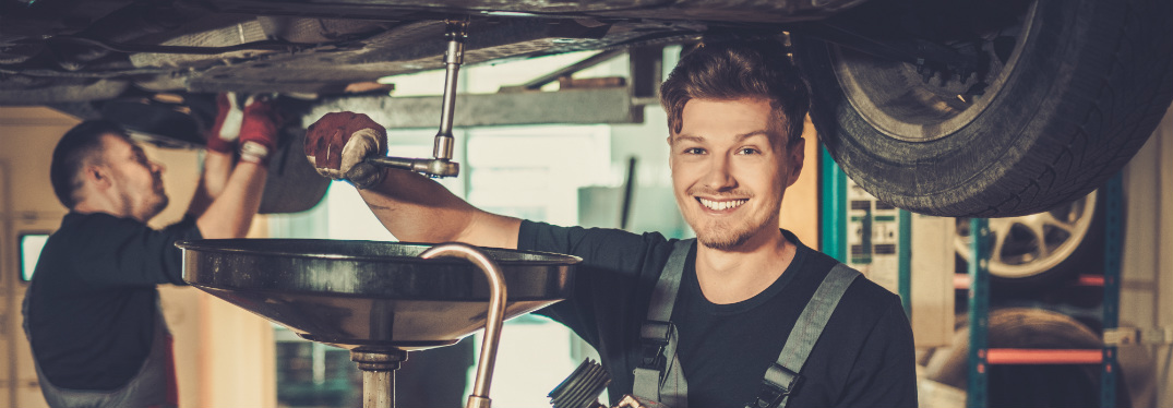 Two male mechanics work on the underside of a car and smile happily.