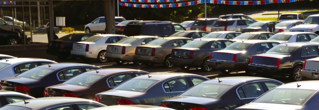 A variety of cars sit on a car lot under a festive red, white and blue banner.