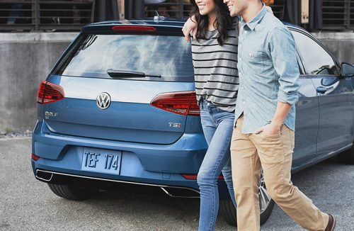 Two walking behind a parked 2019 VW Golf