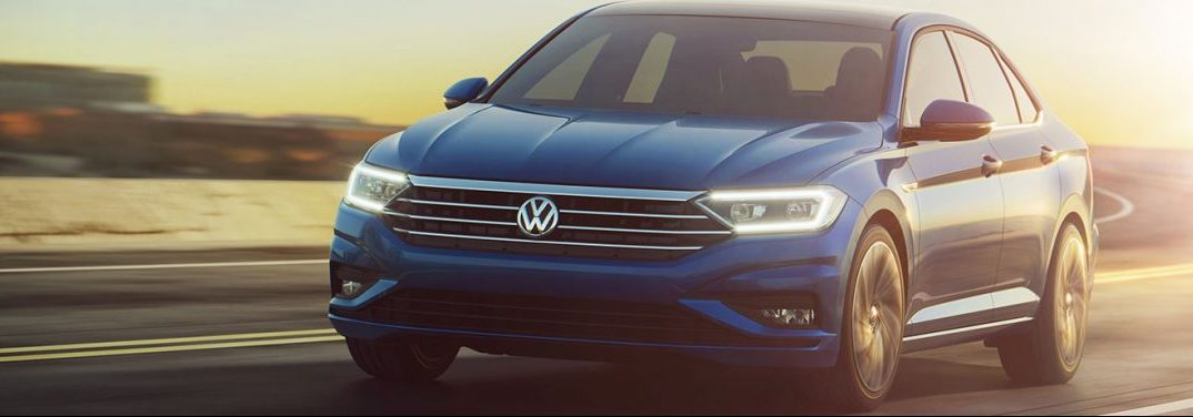 Blue 2019 Volkswagen Jetta cruises up a highway with its daytime running lights activated.