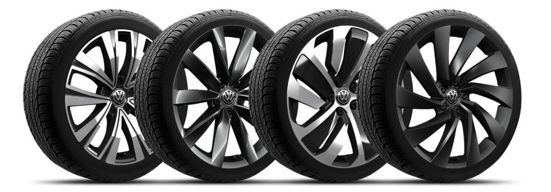 A row of four alloy wheels standing upright on a white background.