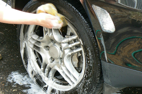 A hand washes an alloy wheel with soap, water, and a sponge.