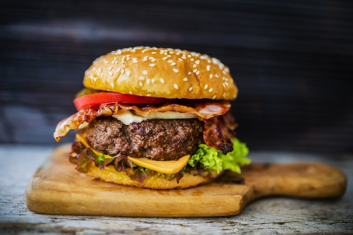 specialty burger on wooden cutting board