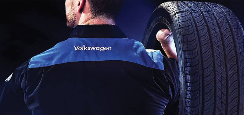 Volkswagen Service tech with tire