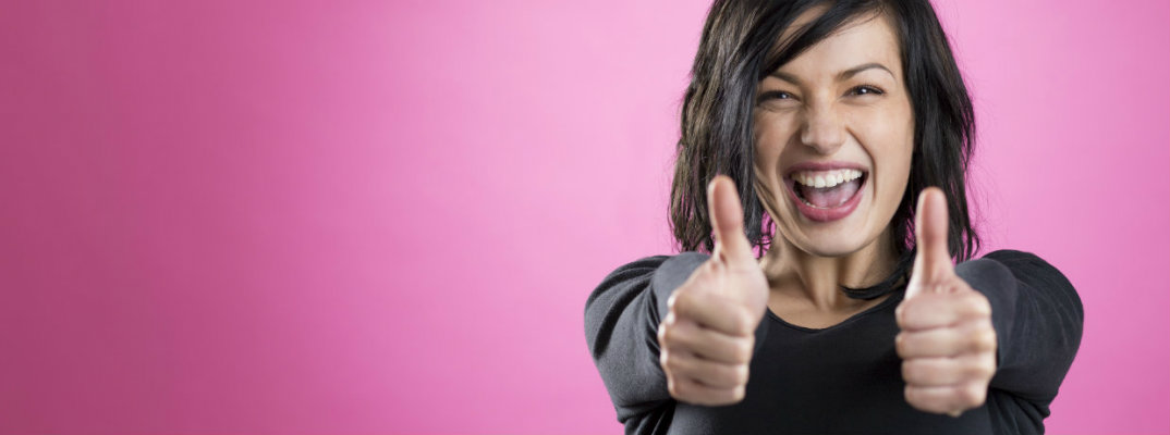 Woman giving a thumbs up with pink background