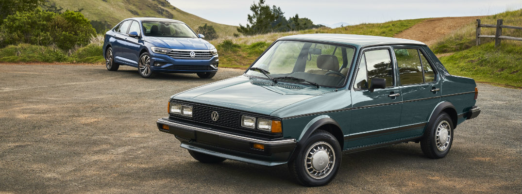 1982 Volkswagen Jetta parked in front of a 2019 Volkswagen Jetta with both models parked on a rocky dirt plain next to grassy hills and a wooden farm fence