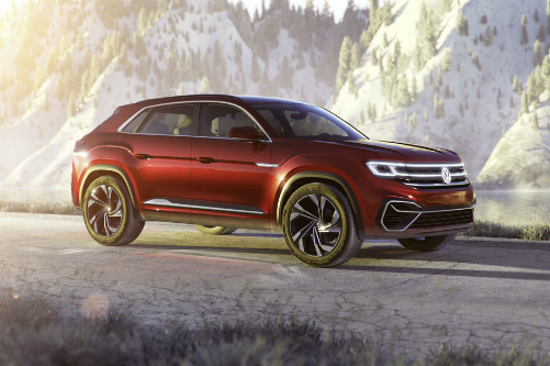 Red Volkswagen Atlas Cross Sport concept vehicle cruises along a highway through snowy mountains.