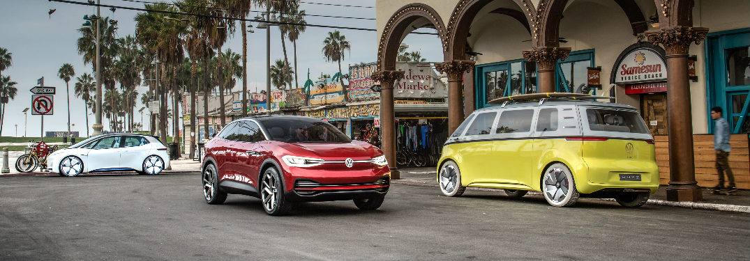 Three Volkswagen I.D. concept vehicles parked in a beach side town