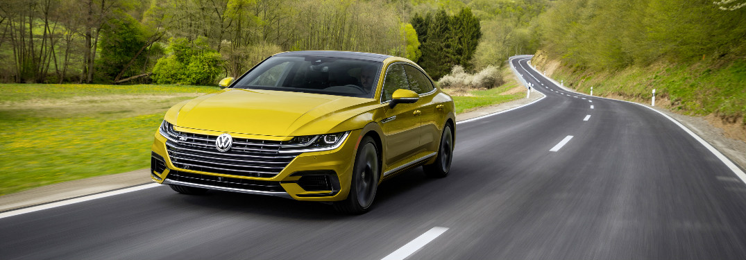 2019 Volkswagen Arteon in bright yellow driving along an empty stretch of road