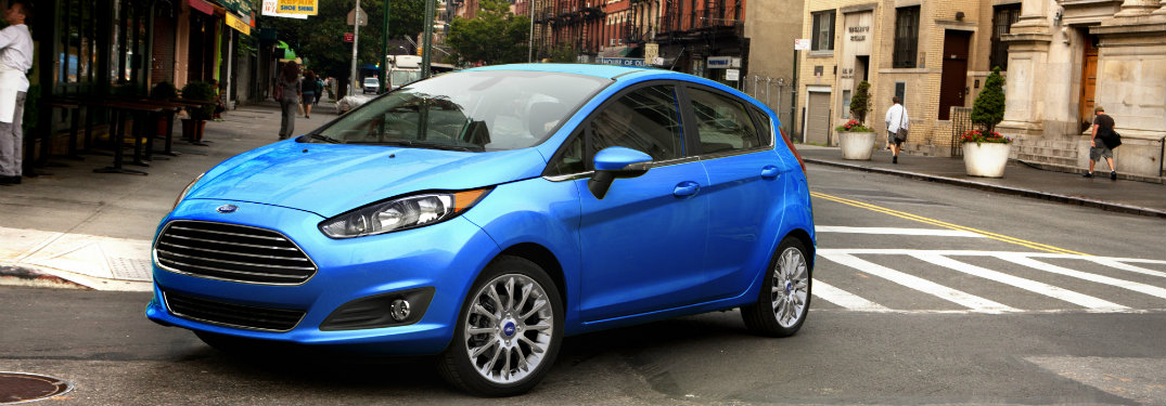 blue ford fiesta parked on city street