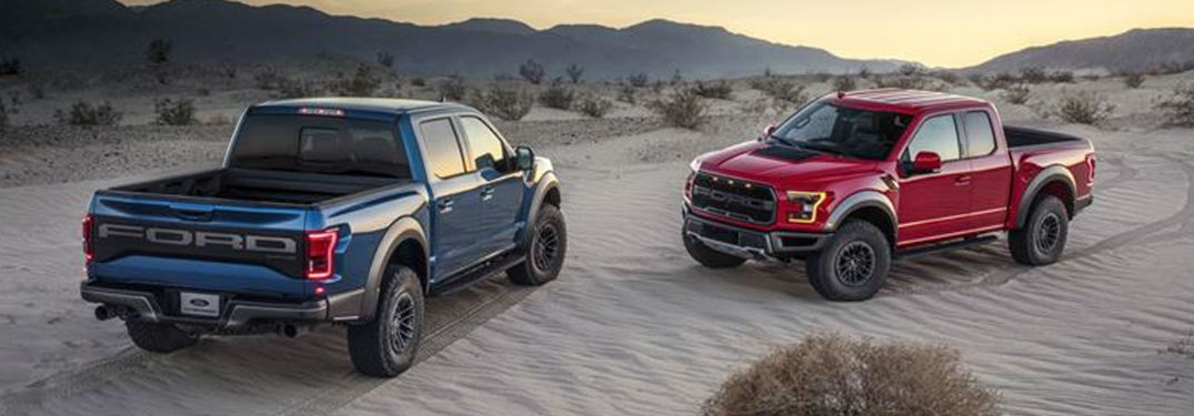a red 2019 Ford F-150 Raptor and a blue 2019 Ford F-150 Raptor parked in the desert
