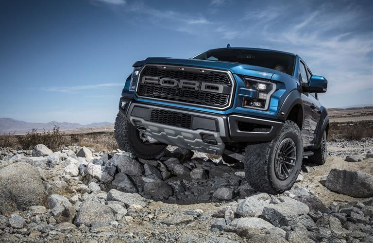 A blue 2019 Ford F-150 Raptor drives over some rocks in the desert.