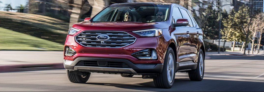 Red 2019 Ford Edge drives down a street in the suburbs.