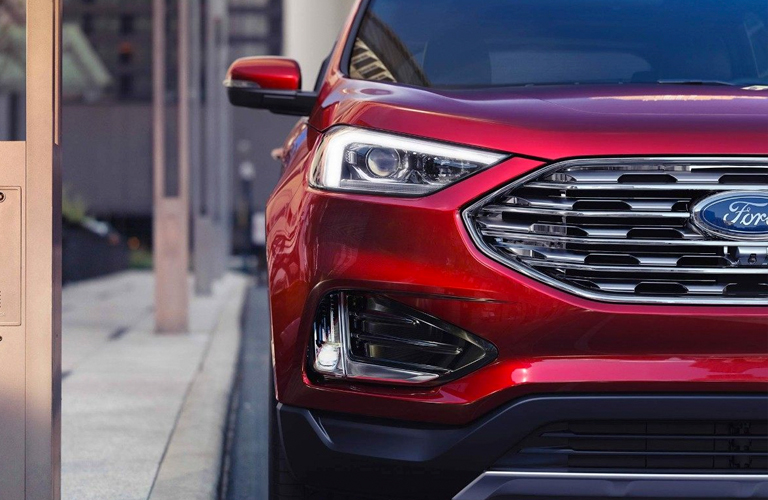 Red 2019 Ford Edge parked by a sidewalk. View of front right half.