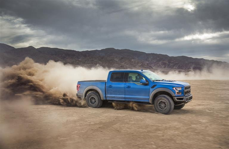 Blue 2019 Ford F-150 Raptor driving in the desert with a cloud of dust behind it.