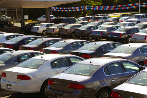 Rows of cars are parked in a dealership lot.