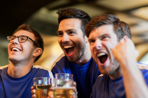 Three men cheer enthusiastically and hold drinks.