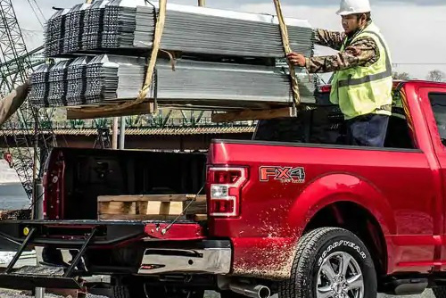A construction worker guides a large load into the bed of a red Ford truck equipped with FX4. The FX4 decal is prominently visible on the side of the vehicle.