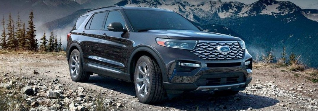Black 2020 Ford Explorer sits outdoors. Exterior front/side angled view. There are snow-covered mountain peaks and pine trees in the background.