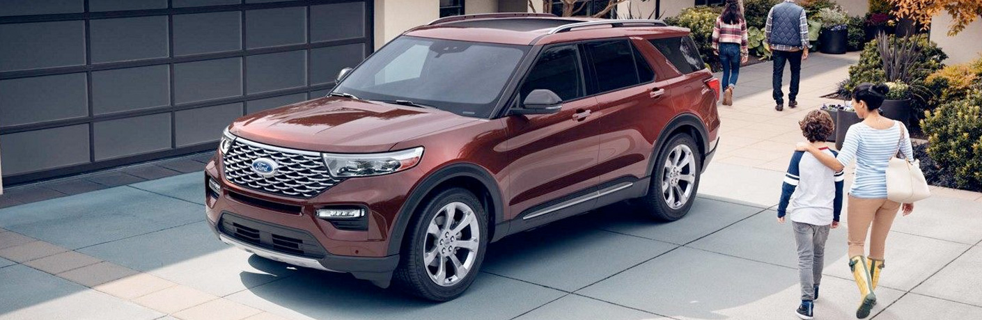 Red 2020 Ford Explorer parked outside a garage with children walking near it.