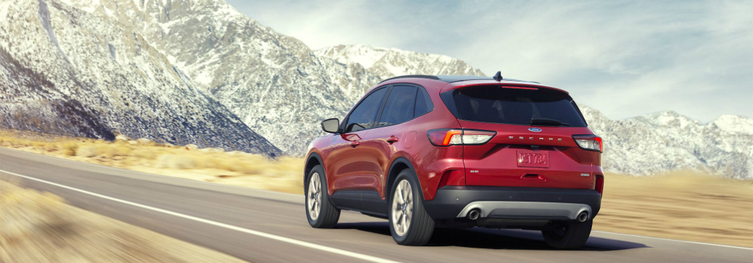 A red 2020 Ford Escape rolls down a highway with a stunning snow-covered mountain backdrop. Exterior rear/side angled view.