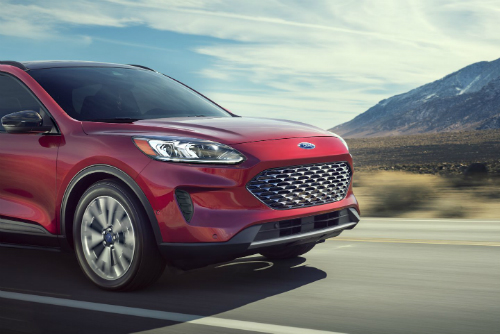 Exterior front/side angled view of a 2020 ford Escape driving down a highway.