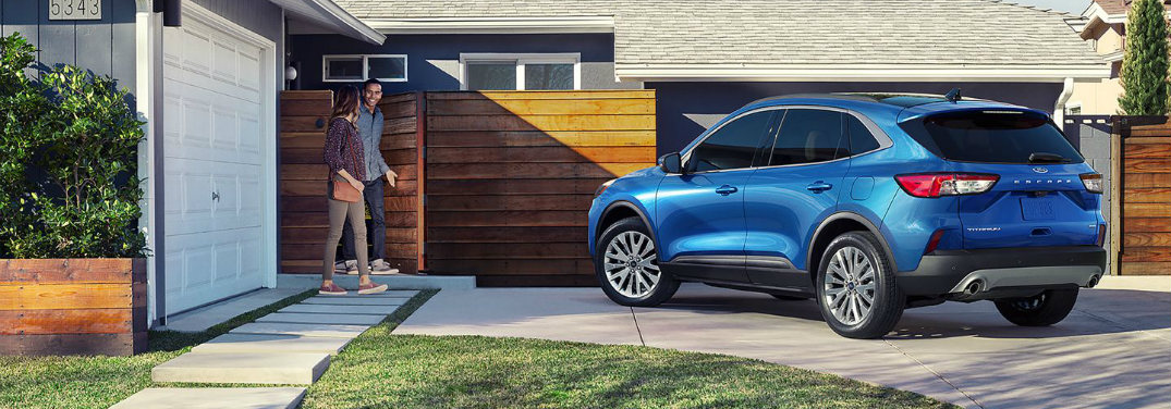 A blue 2020 Ford Escape parked at the top of a driveway of a modern house as an attractive young couple walks out to get inside.