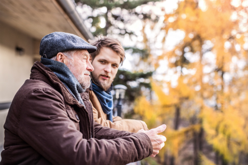 An elderly father and his fully grown son stand on a porch in brisk autumn weather. They converse as the father stares reflectively and contentedly into the distance.