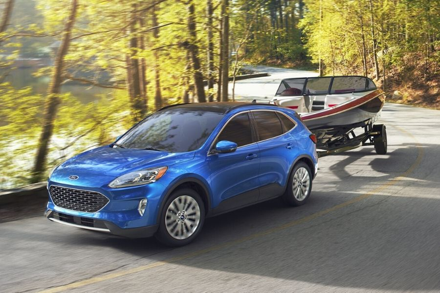Blue 2020 Ford Escape from exterior front drivers side towing boat on road