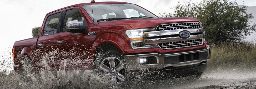 Red 2020 Ford F-150 driving through mud from exterior front passenger side