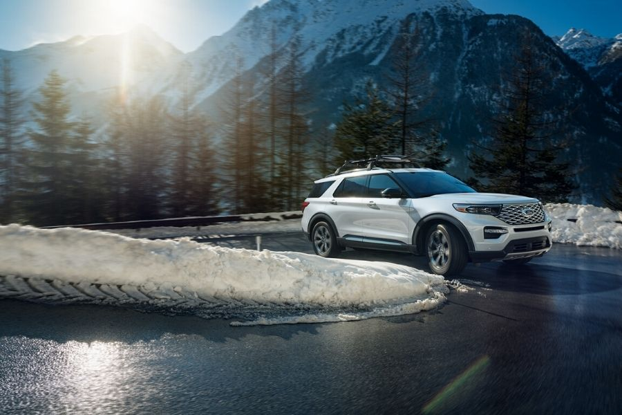 White 2020 Ford Explorer rounding a snowy corner in the mountains from exterior passenger side