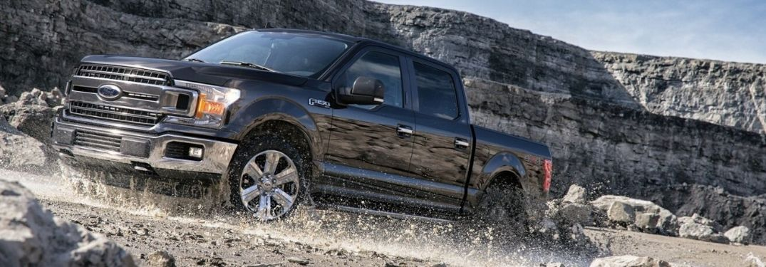 2020 Ford F-150 driving through mud with a cliff in background from front driver side angle