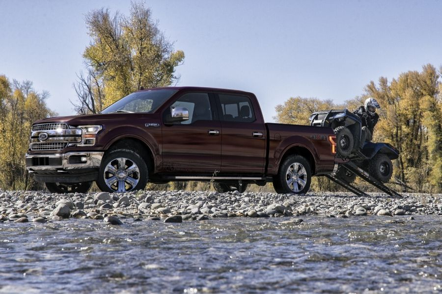 2020 Ford F-150 with person pulling four-wheeler out of bed