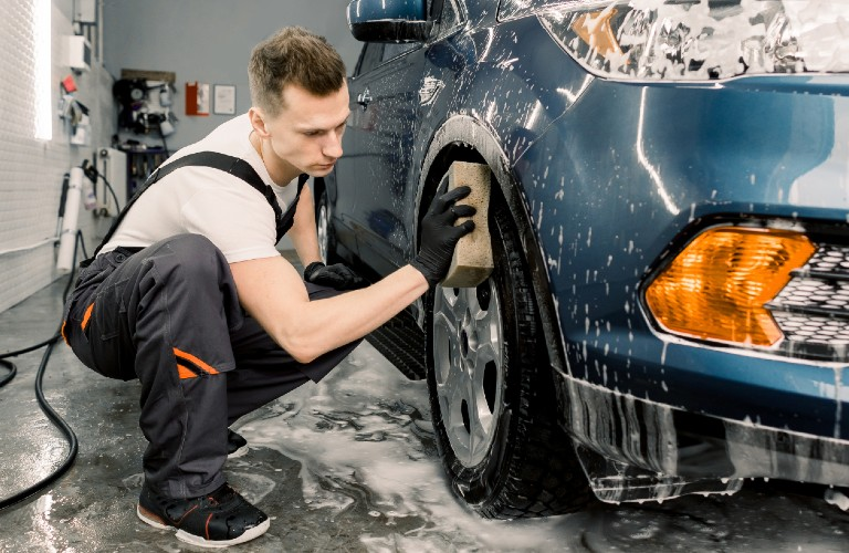 Mechanic cleaning wheel of car