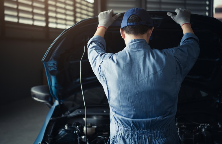 Mechanic looking under hood of a car