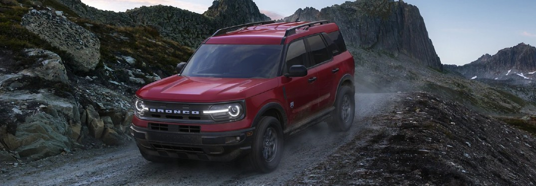 Front driver angle of a red 2021 Ford Bronco Sport driving on a trail