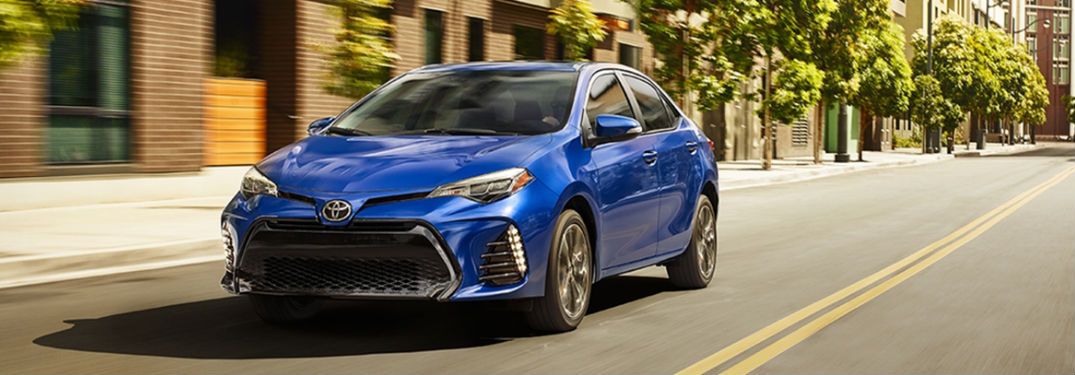 Blue 2018 Toyota Corolla driving down a road