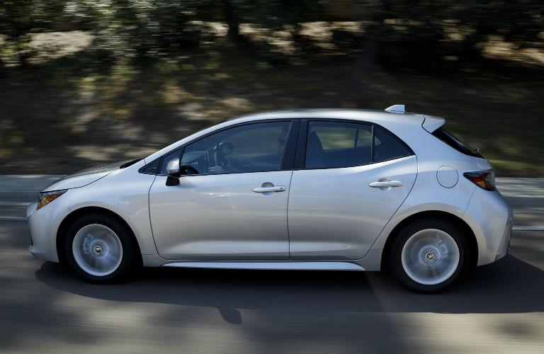 side profile view of silver 2019 Toyota Corolla Hatchback model driving