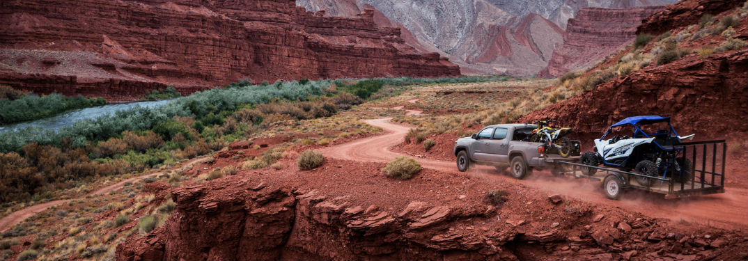 2018 Toyota Tacoma Engine Options and Specs with image of 2018 Tacoma TRD Off-Road towing trailer through a desert canyon