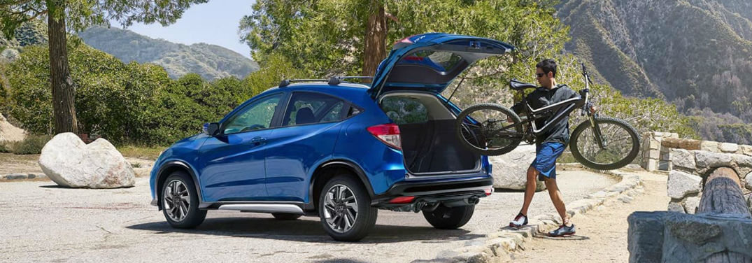 2019 Honda HR-V Pricing and Features with an image of a 2019 Honda HR-V Sport in Aegean Blue Metallic with 18-inch alloy wheels with Honda accessories with a man loading a bike in the cargo area
