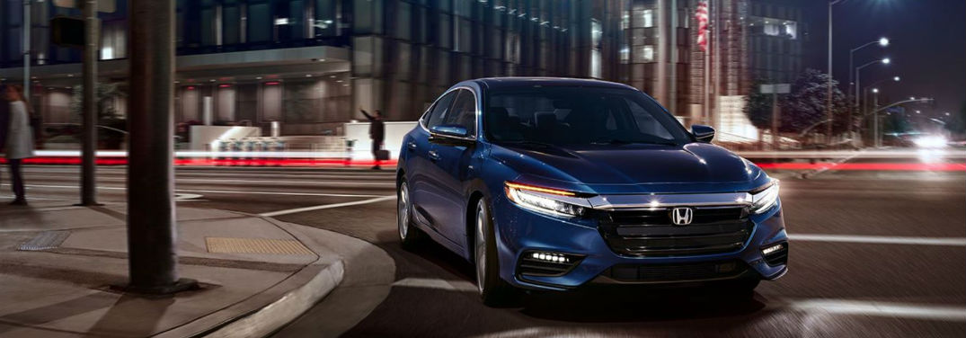 2019 Honda Insight Trim Comparisons with image of a 2019 Honda Insight in Cosmic Blue Metallic turning a corner at night