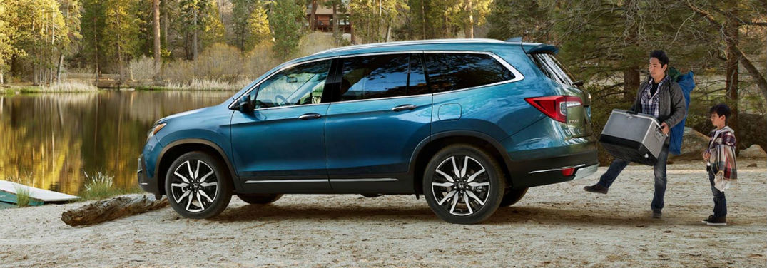 2019 Honda Pilot Pricing and Safety Features with image of a 2019 Honda Pilot parked by a forest lake with a father and son using the hands-free power liftgate to load camping gear