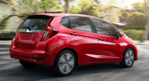 2019 Honda Fit EX-L in Milano Red driving in a neighborhood