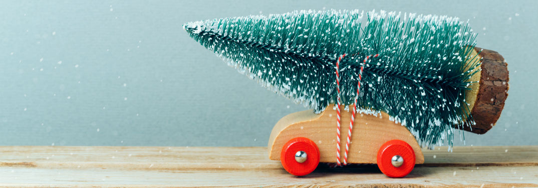 Christmas Tree Farms near Lima OH with image of a toy wooden car with a toy Christmas tree tied on top