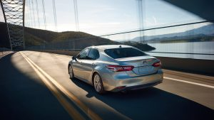 2019 Toyota Camry Hybrid XLE in Celestial Silver Metallic driving on a bridge