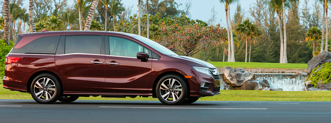 Red 2019 Honda Odyssey driving past palm trees and a waterfall